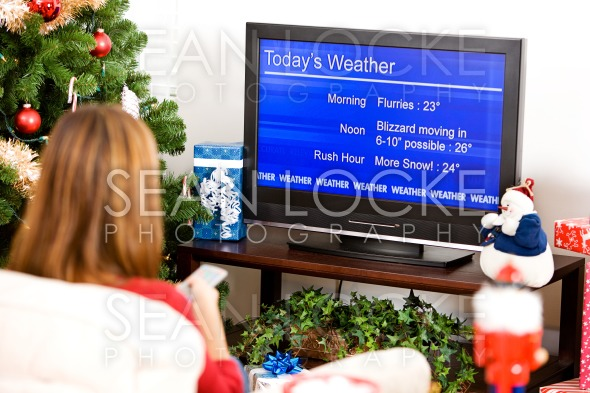 Christmas: Woman Watching Winter Weather Report Stock Photography Content by Sean Locke
