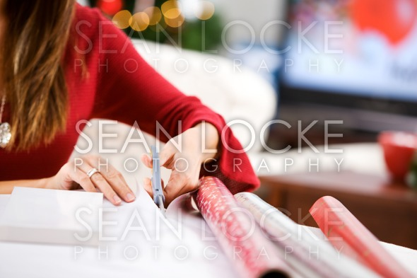 Christmas: Woman Cutting Wrapping Paper Stock Photography Content by Sean Locke