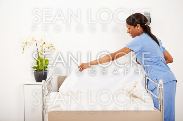 Hospital: Female Nurse Making the Bed Stock Photography Content by Sean Locke