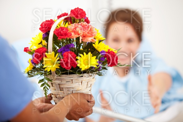 Hospital: Woman Reaches for Flower Gift Stock Photography Content by Sean Locke