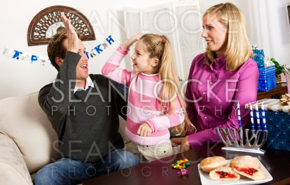 Hanukkah:  Girl High Fives Dad After Winning Stock Photography Content by Sean Locke