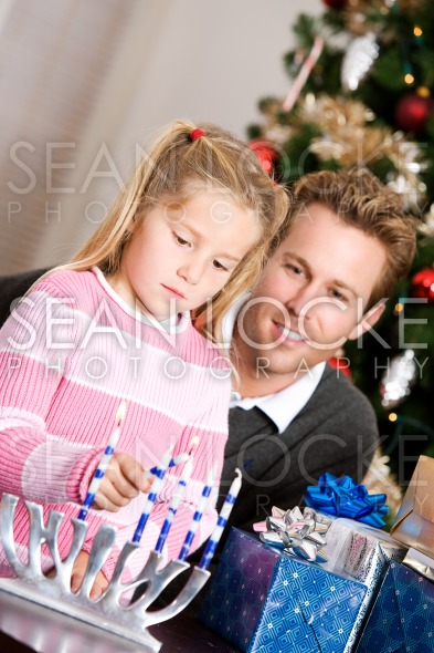 Holidays: Dad Watches Girl Light Candles Stock Photography Content by Sean Locke