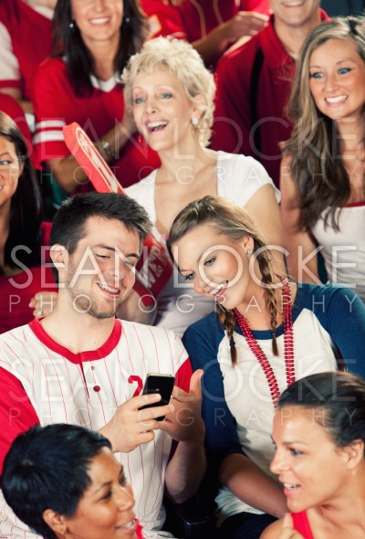 Fans: Man Shows Girlfriend Cell Phone Stock Photography Content by Sean Locke