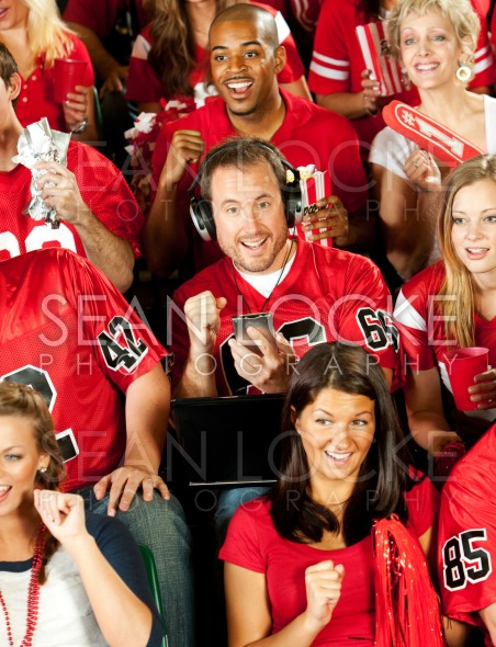 Fans: Man Distracted By Other Sporting Events Stock Photography Content by Sean Locke