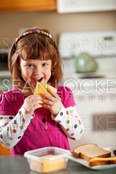 Kitchen Girl: Eating a Slice of Cheese Stock Photography Content by Sean Locke