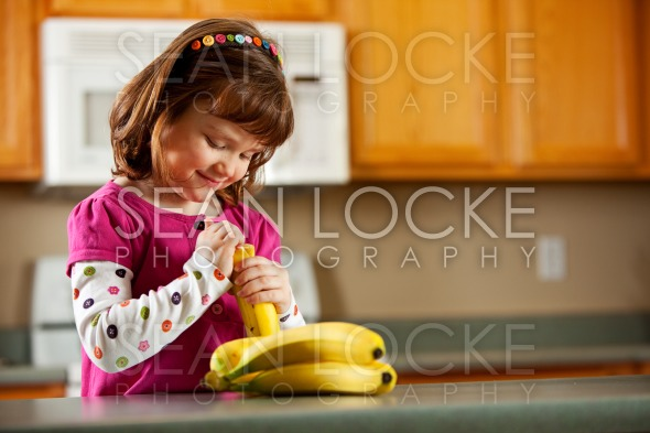 Kitchen Girl: Ready to Eat a Banana Stock Photography Content by Sean Locke