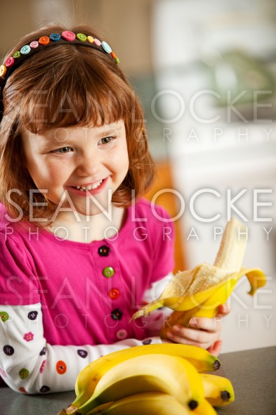 Kitchen Girl: Eating a Banana Stock Photography Content by Sean Locke