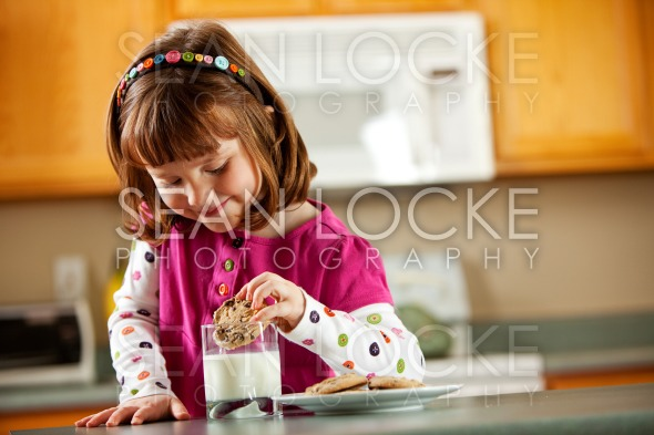 Kitchen Girl: Dunking a Cookie into Glass of Milk Stock Photography Content by Sean Locke