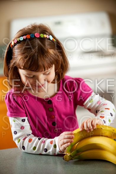 Kitchen Girl: Choosing a Banana Stock Photography Content by Sean Locke