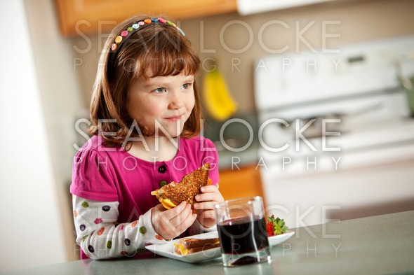 Kitchen Girl: Eating a Grilled Cheese Stock Photography Content by Sean Locke