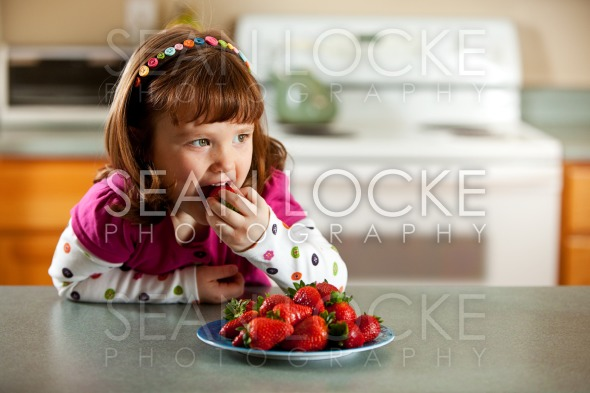 Kitchen Girl: Tasting Strawberries Stock Photography Content by Sean Locke