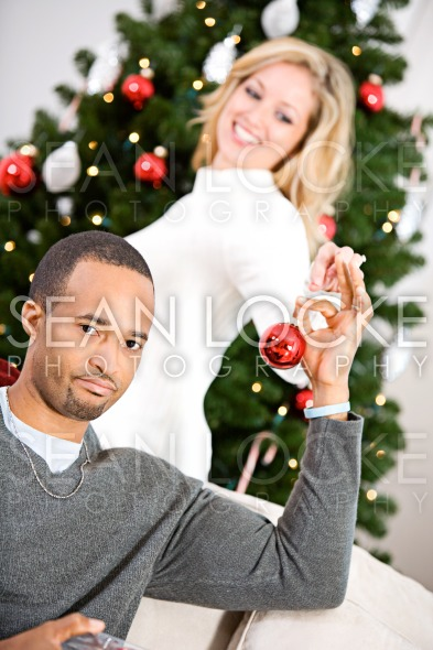 Christmas: Man Helping Woman Decorate Christmas Tree Stock Photography Content by Sean Locke