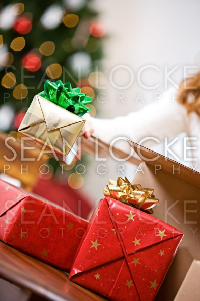 Christmas: Woman Packing Gifts In Shipping Box Stock Photography Content by Sean Locke