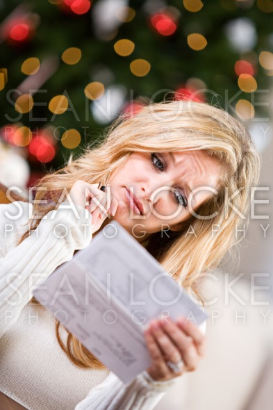 Christmas: Woman Upset At Credit Card Bill Stock Photography Content by Sean Locke