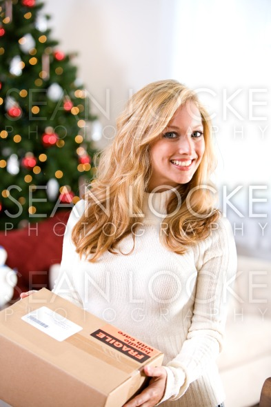Christmas: Woman Holding Shipping Box Stock Photography Content by Sean Locke