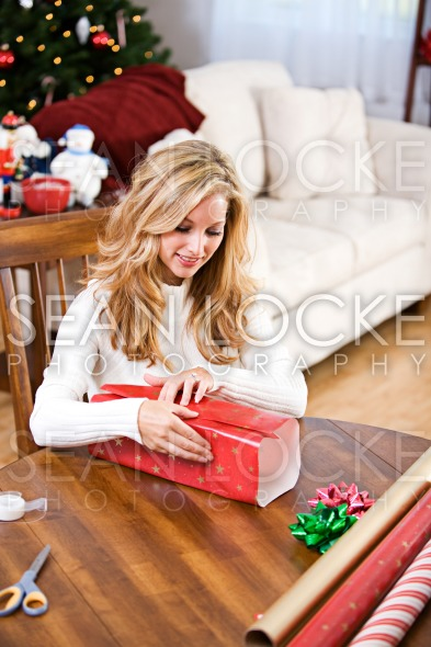 Christmas: Woman Wrapping Christmas Gift Stock Photography Content by Sean Locke