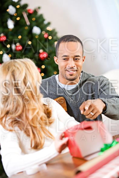 Christmas: Man Wants To Know What's In Box Stock Photography Content by Sean Locke