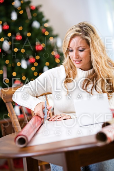 Christmas: Smiling Woman Cutting Wrapping Paper Stock Photography Content by Sean Locke
