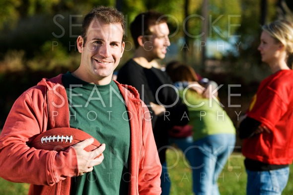 Football: Man Stands with Football and Friends Stock Photography Content by Sean Locke