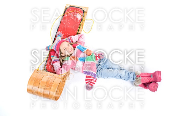 Winter: Little Girl Lying With Snow Stock Photography Content by Sean Locke
