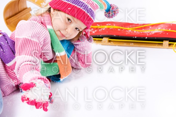Winter: Little Sled Girl With Handful of Snow Stock Photography Content by Sean Locke