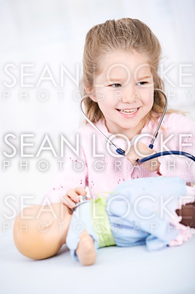 Nurse: Girl Pretends to Check Doll Stock Photography Content by Sean Locke