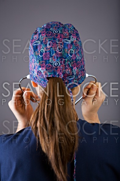 Nurse: Rear View of Nurse Putting on Stethoscope Stock Photography Content by Sean Locke