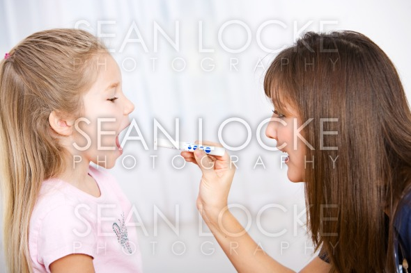 Nurse: Doctor Checks Throat of Girl Stock Photography Content by Sean Locke