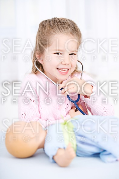 Nurse: Girl Playing Nurse with Doll Stock Photography Content by Sean Locke