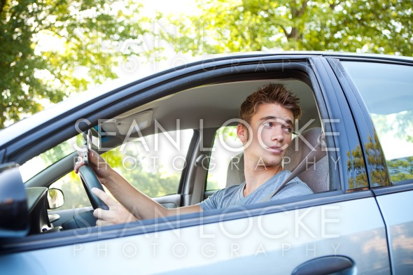 Driving: Driver Turning and Holding Cell Phone Stock Photography Content by Sean Locke