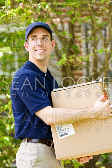 Delivery: Man Walkng with Stack of Packages Stock Photography Content by Sean Locke