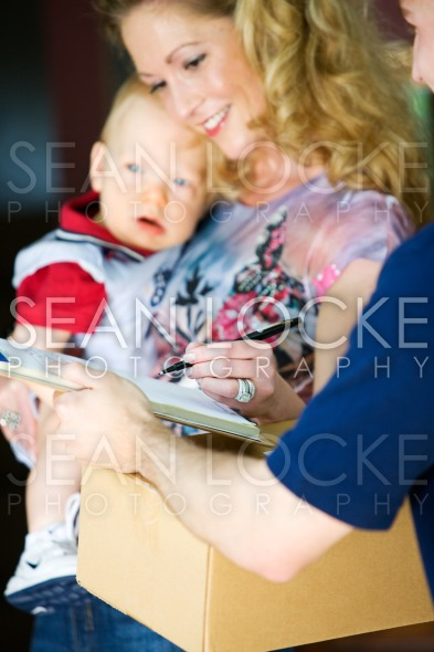 Delivery: Mother Signing for Package Stock Photography Content by Sean Locke