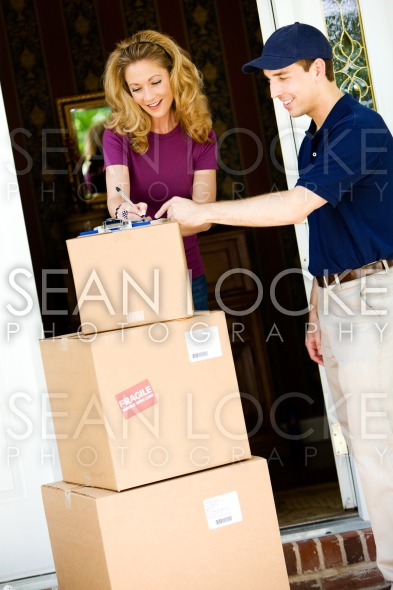 Delivery: Woman Gets Stack of Boxes Stock Photography Content by Sean Locke