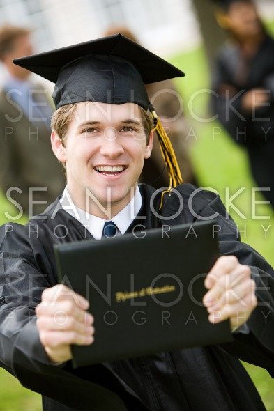 Graduation: Excited Male Holds Up Diploma Stock Photography Content by Sean Locke