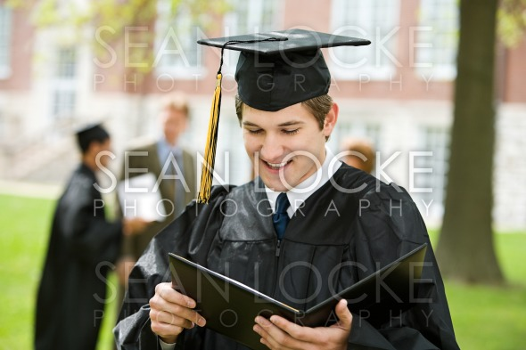 Graduation: Graduate Reads Diploma Stock Photography Content by Sean Locke