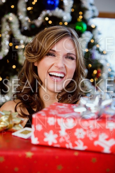 Party: Pretty Woman Holding Christmas Gifts And Laughing Stock Photography Content by Sean Locke