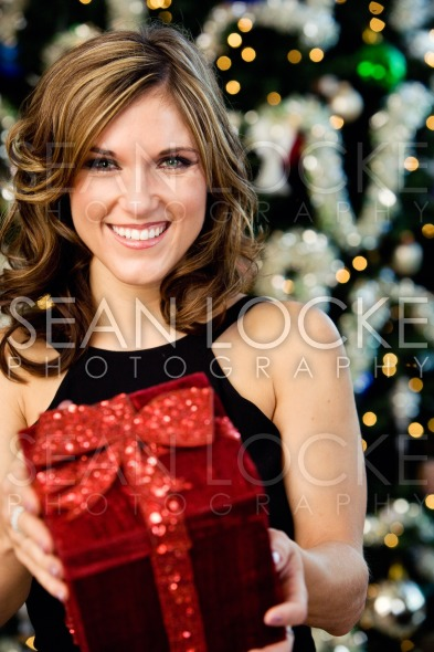 Party: Pretty Woman Holding Christmas Gift Stock Photography Content by Sean Locke