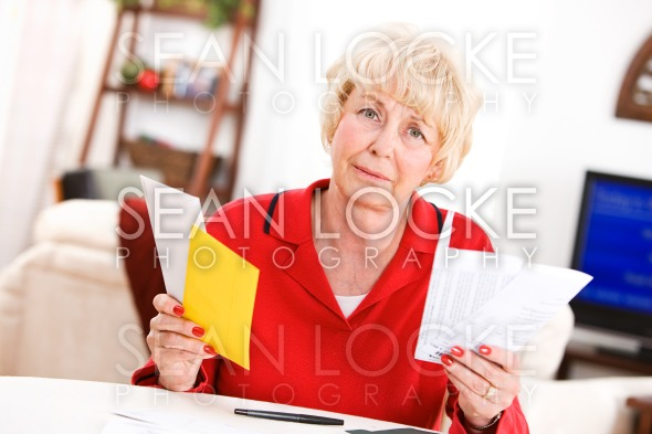 Seniors: Upset Senior Holding Bill Payment Letters Stock Photography Content by Sean Locke