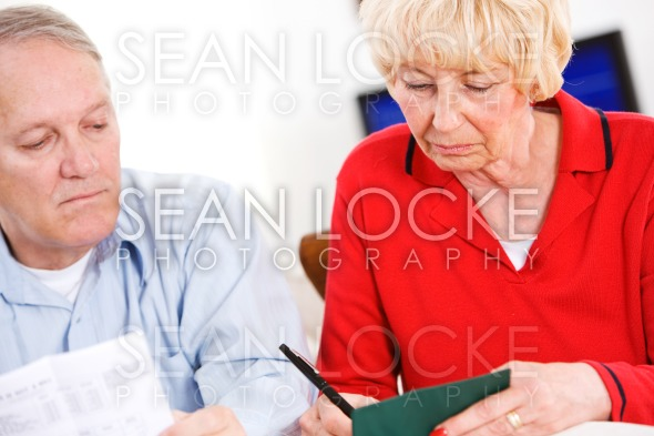 Seniors: Writing Out Checks For Bills Stock Photography Content by Sean Locke