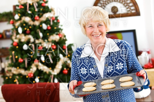 Christmas: Senior Woman Holding Tray Of Holiday Cookies Stock Photography Content by Sean Locke