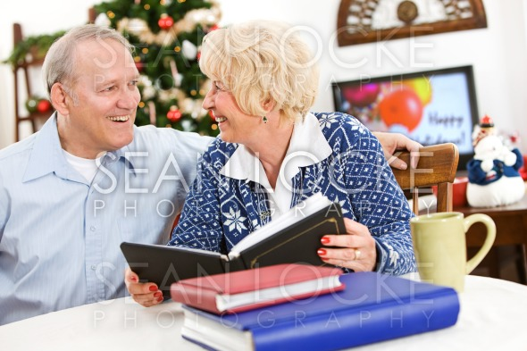 Christmas: Couple Looking at Scrapbooks Stock Photography Content by Sean Locke
