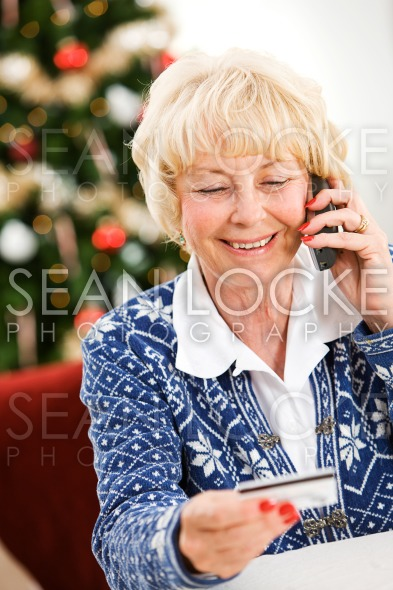 Christmas: Woman Using Credit Card Over Phone Stock Photography Content by Sean Locke