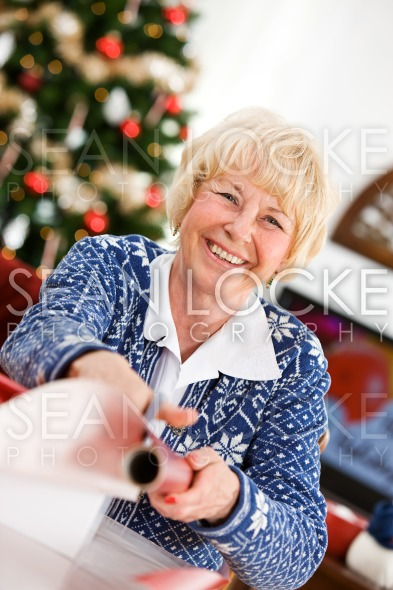 Christmas: Senior Woman Wrapping Gifts Stock Photography Content by Sean Locke
