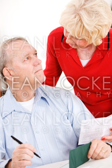 Seniors: Senior Couple Writing Bill Payments Stock Photography Content by Sean Locke
