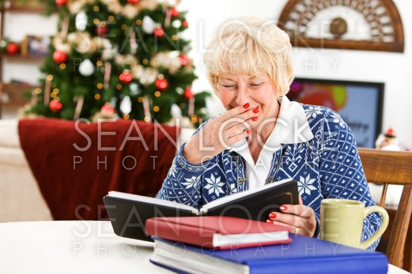 Christmas: Senior Woman Looks At Photo Albums Stock Photography Content by Sean Locke