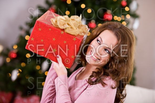 Christmas: Woman Trying To Guess Christmas Gift Stock Photography Content by Sean Locke