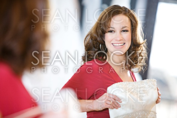 Bride: Woman Holds Up Gown While Looking In Mirror Stock Photography Content by Sean Locke