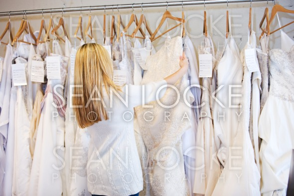 Bride: Woman Browsing Through Rack Of Wedding Gowns Stock Photography Content by Sean Locke