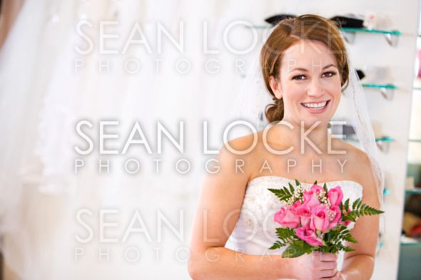 Bride: Woman Holding Bouquet Trying On Wedding Gown Stock Photography Content by Sean Locke