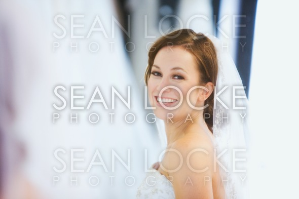 Bride: Pretty Woman Wearing Veil Looks In Mirror Stock Photography Content by Sean Locke